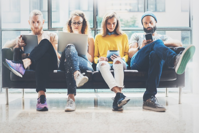 Group Adult Hipsters Friends Sitting Sofa Using Modern Gadgets.Business Startup Friendship Teamwork Concept.Creative People Working Together Marketing Project.Coworking Process Office Studio.Blurred.